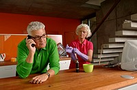 Senior man on the phone while his wife is putting on rubber gloves