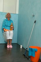 Senior woman next to cleaning utensils sitting on a toilet