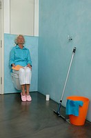 Exhausted senior woman sitting on toilet bowl