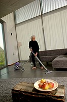 Senior woman vacuuming living room