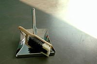 Small broom and metallic shovel on the floor, high angle view