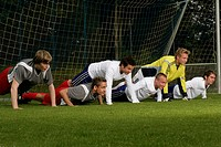 Six young footballers doing push_ups in front of a goal on a pitch