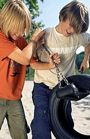 Two Boys pulling the Chains of a Rubber Tire_Swing _ Fun _ Common Ground _ Leisure Time _ Playground