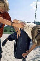 Blonde Boy pushing a Rubber Tire_Swing on which his Friend lies procumbently _ Friendship _ Fun _ Playground