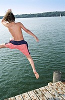 Boy jumping into Water from a wooden Footbridge _ Salutation _ Fun _ Summer _ Swimming