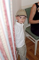 Little Boy with a Cap standing next to a Curtain _ Childhood _ Look