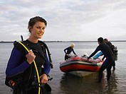 Young woman with diving equipment on standing next to an inflatable boat with friends in background