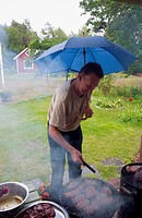 Man Grillar Kött Utomhus Under Ett Paraply, Man Grills Meat Outdoors With Umbrella In One Hand