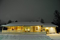 Upplyst villa i vinterlandskap kvällstid. Villa In Snow With Lights On, Winter Night, Low Angle View