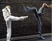 Två unga kvinnor tränar kickboxning Young woman kick boxing, side view