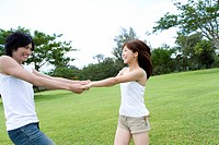 Young couple holding hands on lawn, smiling, Saipan, USA