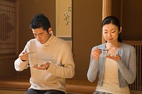 Japanese couple taking Wagashi in tea room, front view, Japan