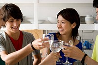 Four young people toasting with wineglasses in kitchen, smiling