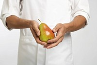 Chef holding pear mid section
