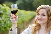 Young woman holding glass of red wine in vineyard portrait (thumbnail)