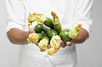 Chef holding zucchinis mid section