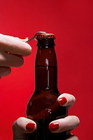 Young woman's hands opening bottle of beer close_up
