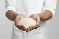 White rice on chef's hands mid section