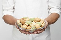 Chef holding bowl of nuts mid section