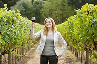 Young woman holding glass of red wine in vineyard portrait