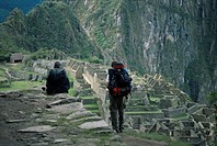 Backpackers look at the Inca ruins at Machu Picchu, UNESCO World Heritage Site, Peru, South America