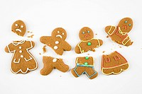 Four frowning male and female gingerbread cookies broken into pieces