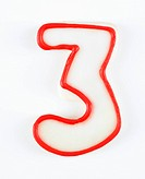 Sugar cookie in the shape of a number three outlined in red icing