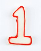 Sugar cookie in the shape of a number one outlined in red icing