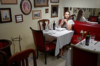 Woman sitting at dining table in restaurant