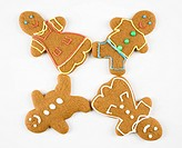 Four male and female gingerbread cookies arranged with feet touching
