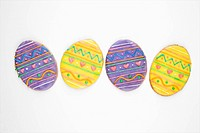 Four sugar cookies in shape of Easter eggs with decorative icing