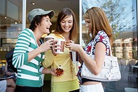 Three teenage girls drinking take_out coffees and eating cakes