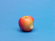 Single apple with bite mark, blue background