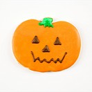 Sugar cookie in shape of jack o lantern with decorative icing