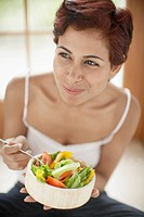 Woman eating salad high angle view
