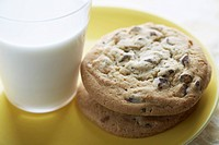 Chocolate chip cookies beside glass of milk close_up