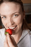 Young woman eating strawberry portrait