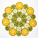 Assorted fruit slices arranged in pattern on white background
