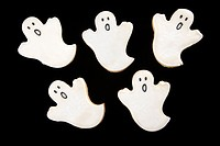 Five sugar cookies in shape of ghosts with decorative icing