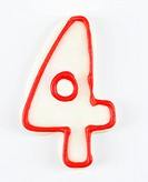 Sugar cookie in the shape of a number four outlined in red icing.