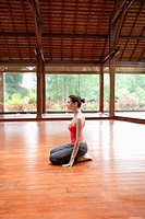 Young woman in sports clothing sitting on wooden floor (thumbnail)