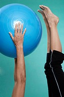 Mature woman exercising with Swiss ball close_up