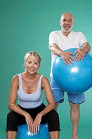 Senior man and mature woman with Swiss balls