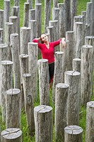 Young woman surrounded by stumps, high angle view