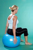 Mature woman exercising on Swiss ball rear view