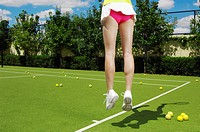 Female tennis player jumping low section