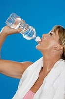 Fit mature woman drinking water