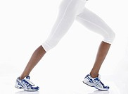 Woman in sports clothing stretching legs low section
