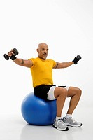 Mid adult multiethnic man balancing on blue exercise ball with outstretched arms holding dumbbells and looking at viewer