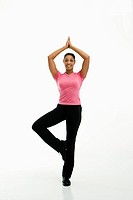 Mid adult multiethnic woman wearing exercise clothing standing in yoga tree pose smiling at viewer